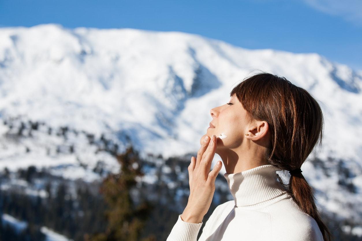 femme appliquer crème solaire ski montagne