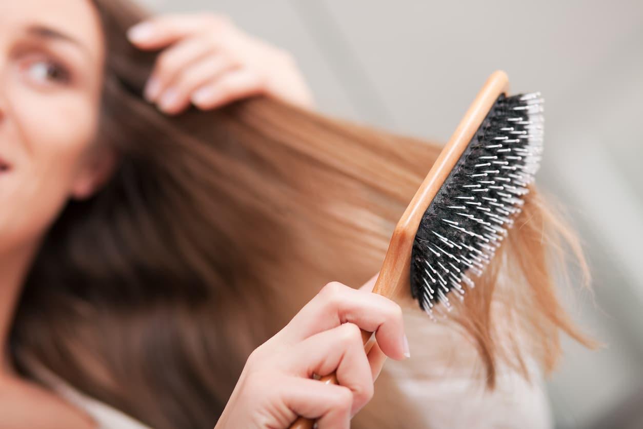 femme se coiffer brosse en bois