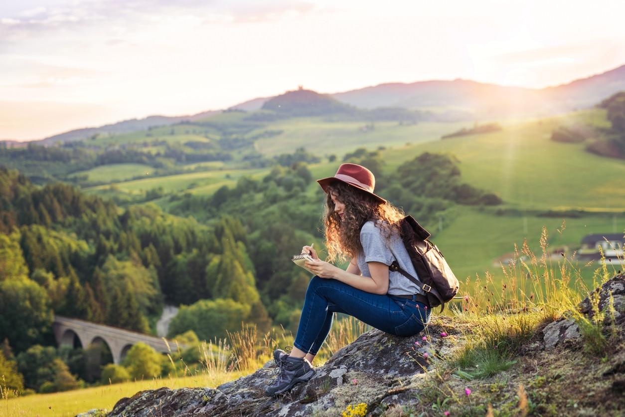 touriste femme voyage écovolontariat sac à dos montagne nature