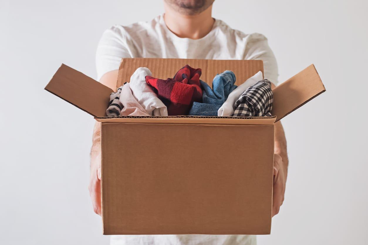 homme donner recycler vêtements carton don